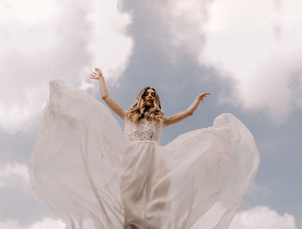 Modern Bride on a rooftop with blue sky and clouds in the background