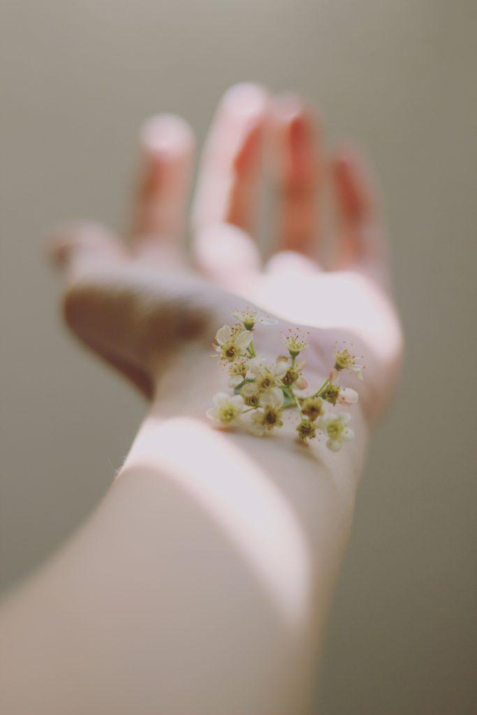 Ausgestreckter Arm auf dem Blüten liegen